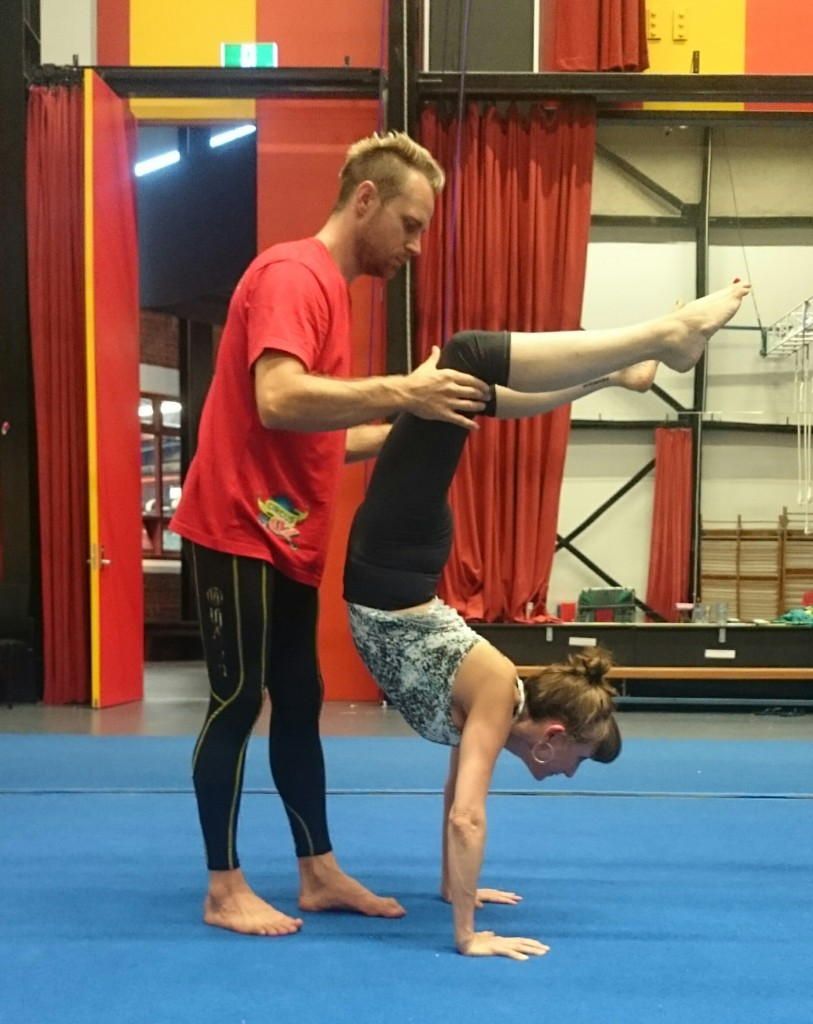 Circus Oz instructor Zeb helps Anna into a bend