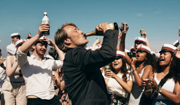 Mads Mikkelsen drinking from a bottle