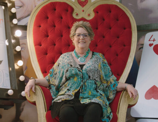 lady sits on throne nest to giant playing card