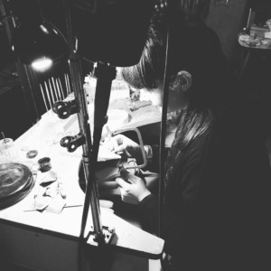 B&W photo of Sophie working on a piece at her bench